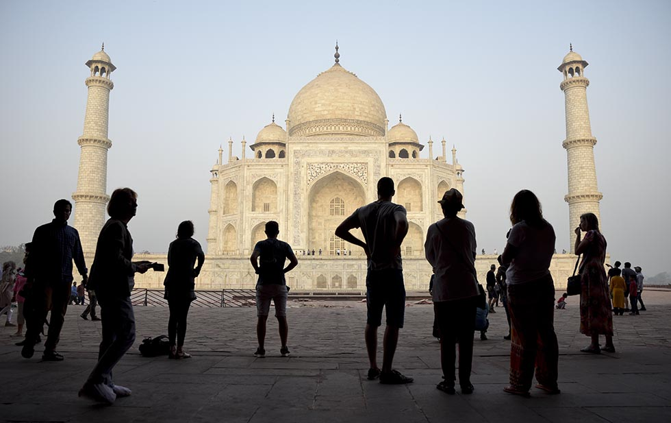 FILE - In this March 22, 2018 file photo, tourists visit India's famed monument of love, the Taj Mahal, in Agra, India. India's top court has on Wednesday, July 11, flayed the federal government for a second time within weeks for lethargy in taking steps to protect the Taj Mahal, the shining white monument to love. The Supreme Court orders the government to furnish full details of the steps being taken and action required for protecting the monument.  (AP Photo/R.S. Iyer, File)